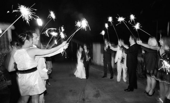 bridal party and guests celebrate Mr. and Mrs. with sparklers