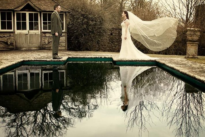 Bride and groom look at each other, reflections off pool