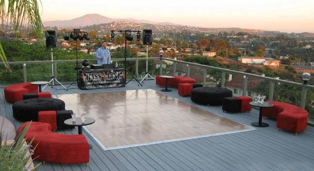 Outdoor wedding on deck with dance floor, and red and black circular couches