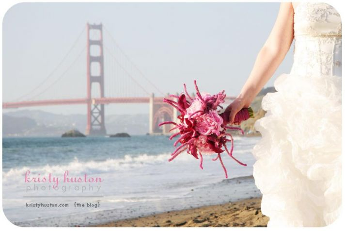Bride's bouquet and dress on San Fran beach, ocean and Golden Gate Bridge in background