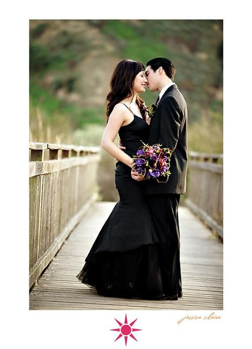 Bride in black wedding dress kisses groom holds vibrant purple and fuschia