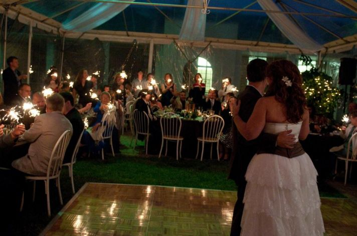 Wedding guests hold sparklers as the bride, in a strapless, tiered white dress with brown sash, and