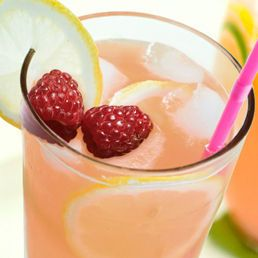 Pink lemonade in a tall glass, garnished with lemon and raspberries.