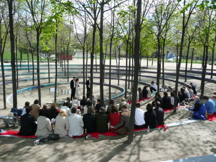 The outdoor ceremony is viewed by wedding guests sitting in a circle.
