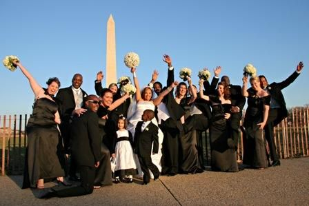 Bride, groom, entire wedding party jump up outside in front of local monument