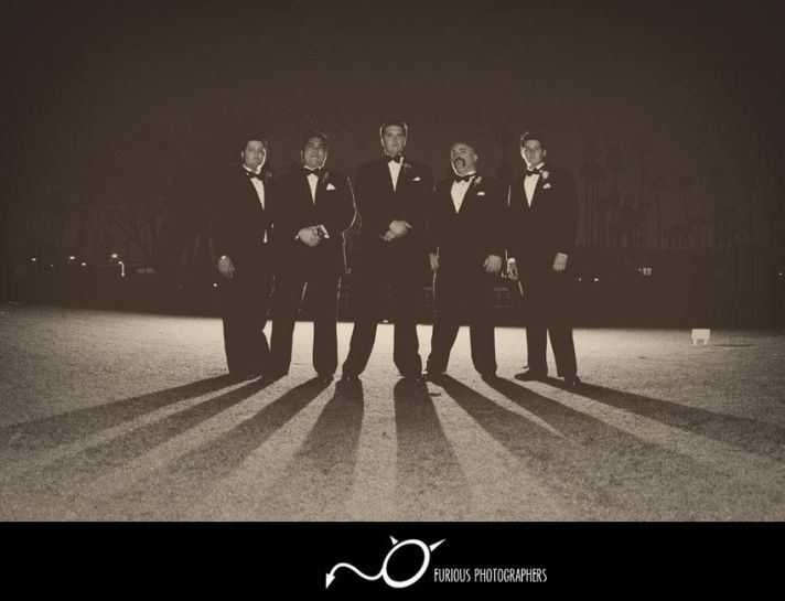 Groom with groomsmen pose together in this black and white wedding photo; outside in parking lot at