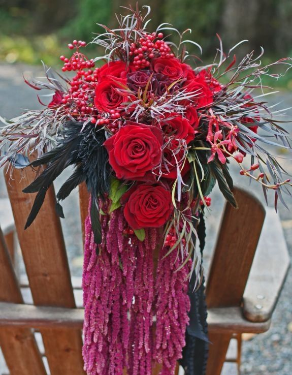 Gorgeous bridal bouquet with dark red roses, hanging plants, and fall/winter details