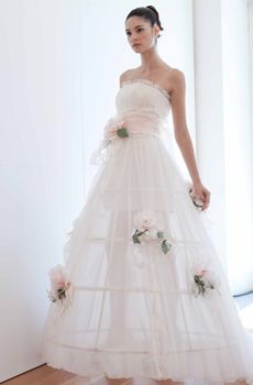 White strapless wedding dress with full a-line skirt, light cotton candy pink rose details and sash