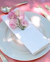 White and pink tablescape at wedding reception- white charger plate and napkin, bubble gum pink flow
