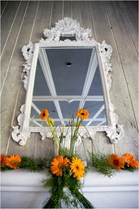 Wedding detail shot: antique white framed mirror, vibrant orange flowers