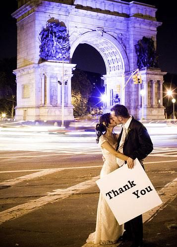 Bride and groom kiss under beautiful arch, hold thank you sign