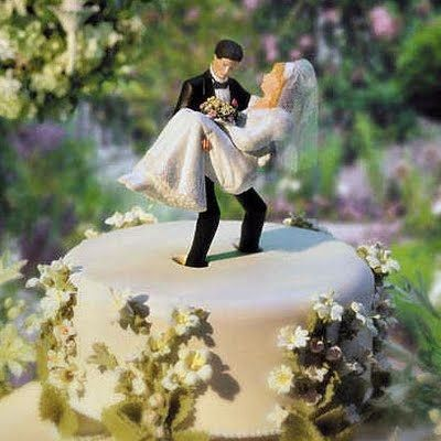 This white cake has a humorous cake topper showing a groom trying to lift a heavy bride.