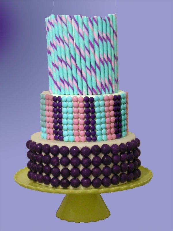 This two tiered wedding cake in shades of pink, purple, and blue is decorated with candy.