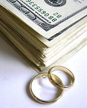 This stack of money with gold wedding bands next to it shows how money affects your wedding planning