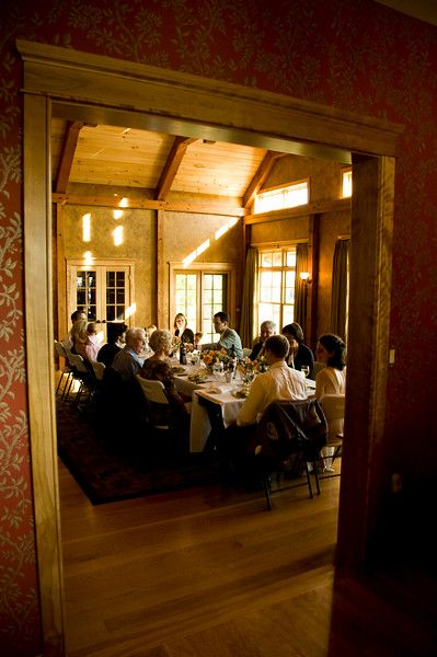 This small wedding party is dining informally in a rustic setting showing a wedding trend.