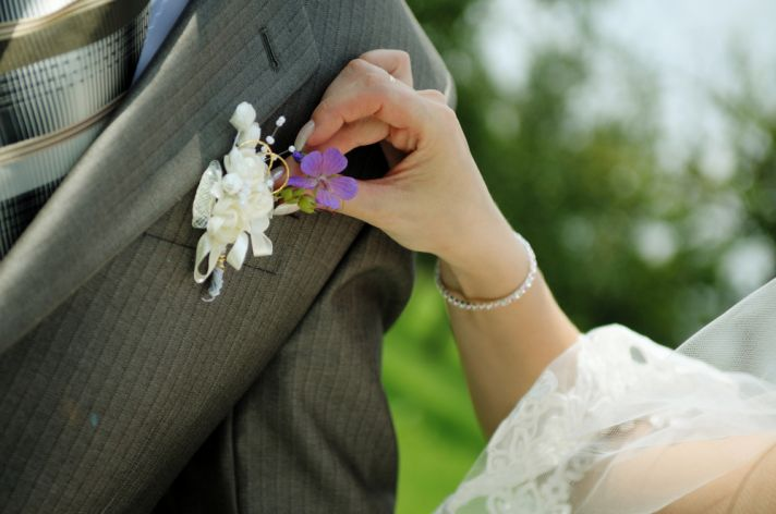 This groom in a grey suit with a purple and white boutonniere is probably tired fo people fixing his