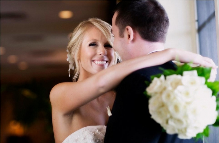 adorable-smiling-bride-in-strapless-ivory-beaded-wedding-dress-ivory-rose-bridal-bouquet-holds-groom
