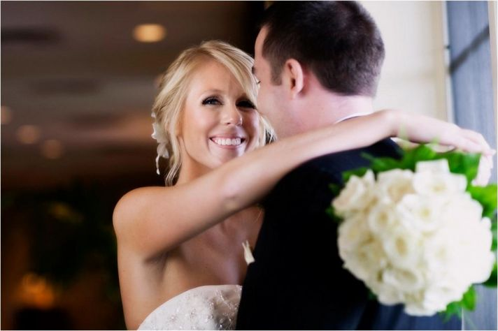 Beautiful bride holds ivory rose bridal bouquet and her handsome groom