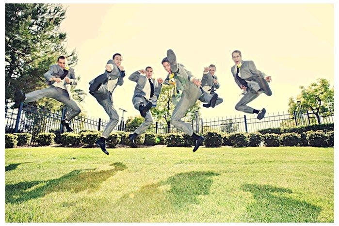 Casual groomsmen jump, ninja style, in green open field for this fun wedding day action shot