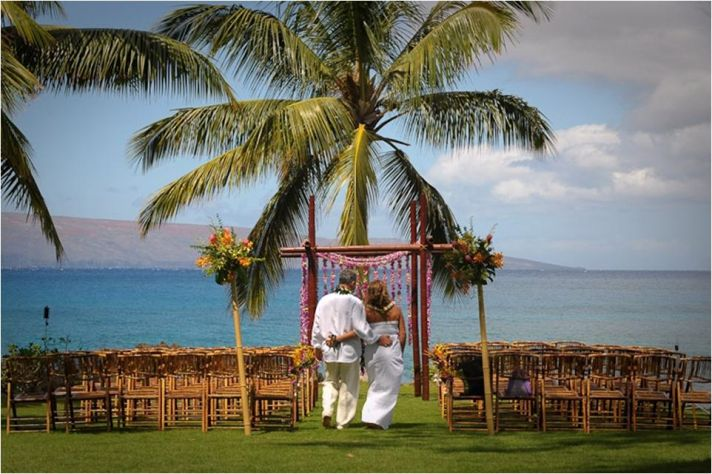 Casually dressed bride and groom hold one another under flower-adorned wedding arbor