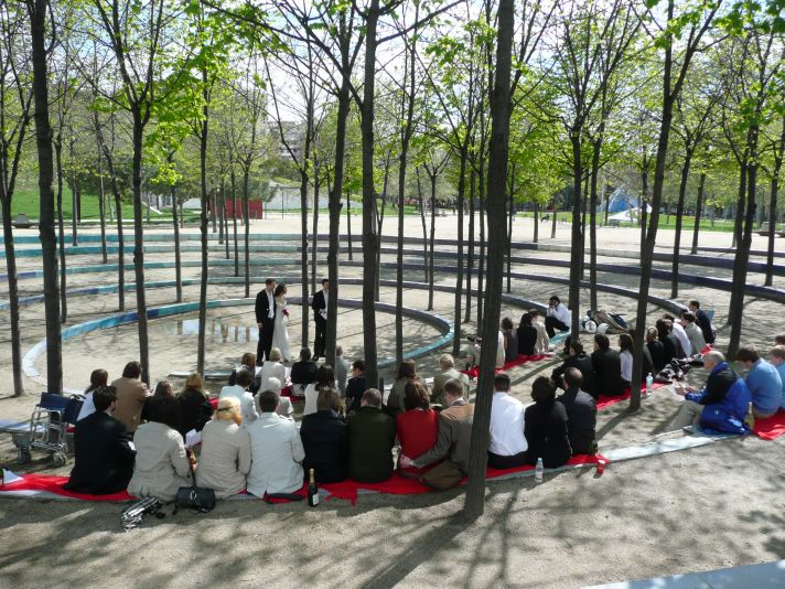 The guests at this outdoor wedding ceremony are seated in a circle in somewhat casual clothing.