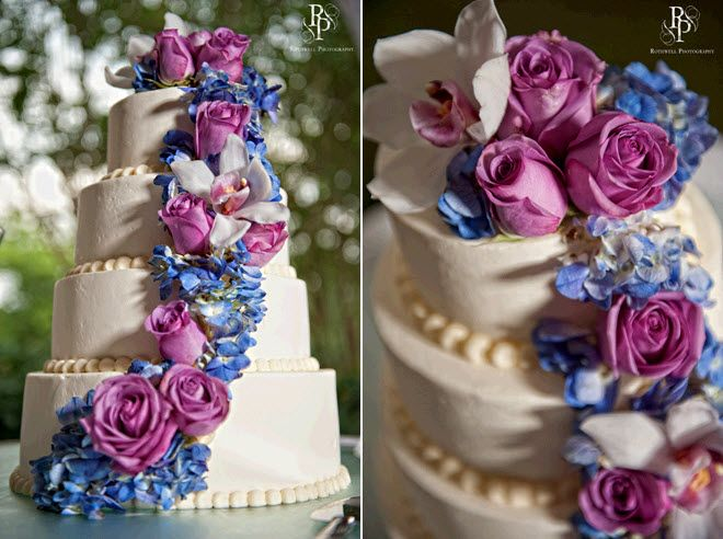 Ivory fourtier stacked wedding cake adorned with fuchsia roses and