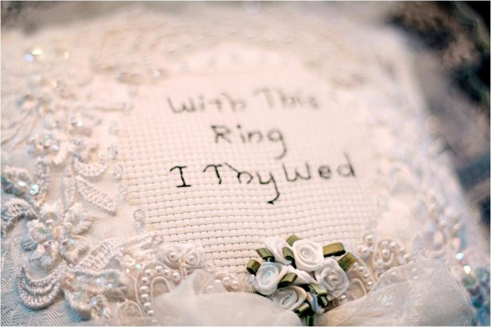 White handmade ring bearer pillow that reads With This Ring I Thy Wed