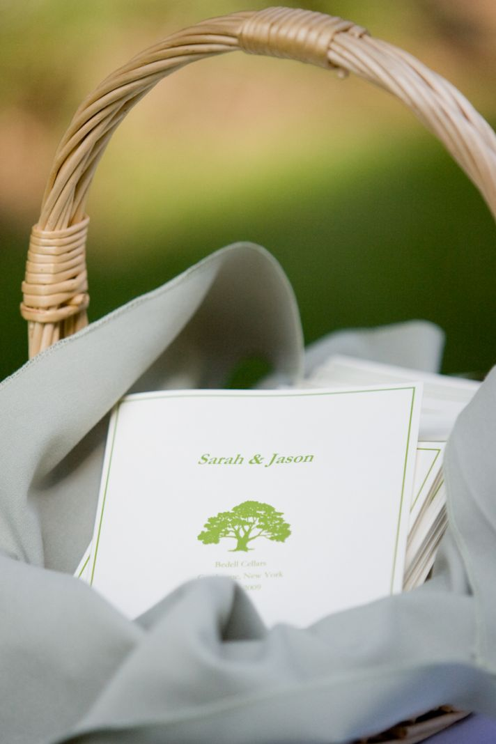This basket of wedding programs features cream programs with sage green writing and a delicate tree