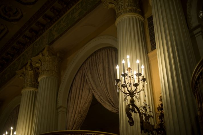 Ornate wedding reception venue with antique chandeliers and candelabras