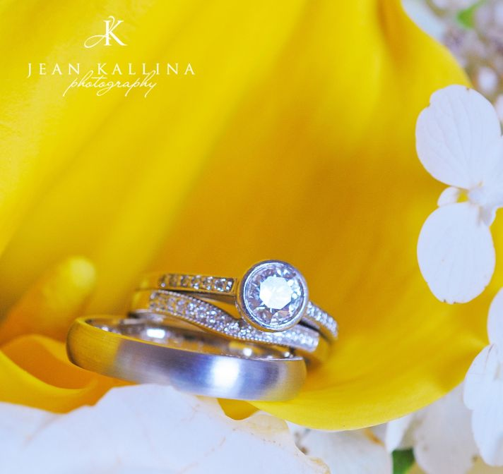 Platinum wedding band and diamond engagement ring shot atop yellow and white vibrant flower
