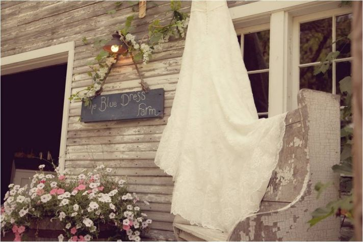 Bride's ivory lace wedding dress hangs outside Blue Barn wedding venue