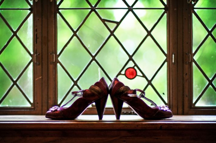 Bride's eggplant purple bridal heels photographed in castle window