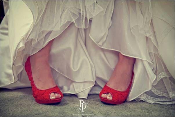 Bride wears ivory wedding dress and red peep-toe bridal heels