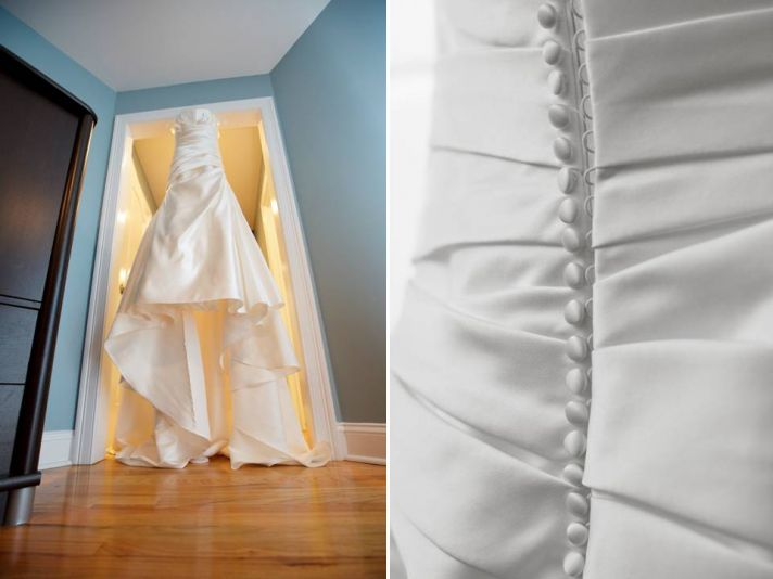 White strapless wedding dress with covered buttons in back hangs in doorway