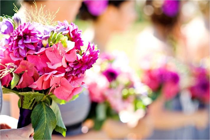 Bright vibrant wedding flowers at outdoor summer wedding ceremony