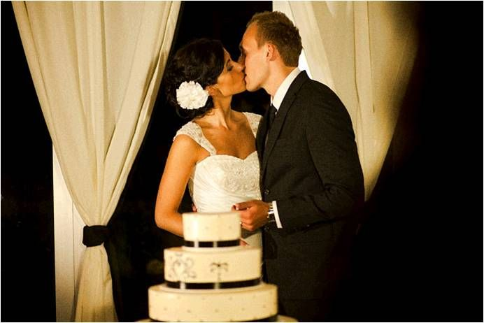 Bride and groom kiss by white classic wedding cake, bride wears white flower in hair