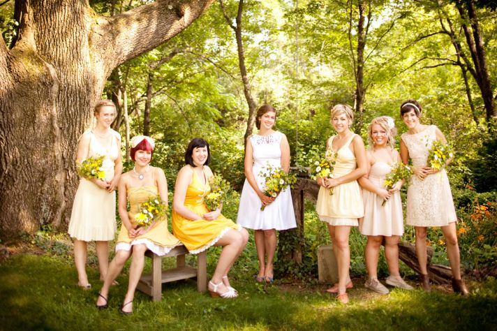 Retro bridesmaids pose outside with bride, wearing mix and match bridesmaids dresses