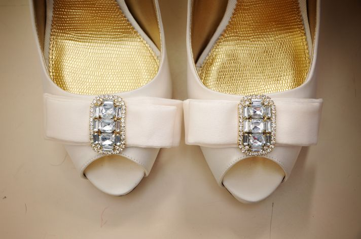 Bride wears ivory satin peep-toe bridal heels with rhinestone and bow details