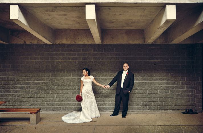 Bride and groom pose together wearing wedding dress and tux with urban backdrop