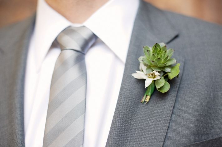 Dapper groom wears grey tailored suit and succulent boutonniere