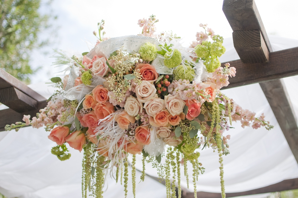 outdoor wedding ceremony arbor with peach ivory and blush pink flowers