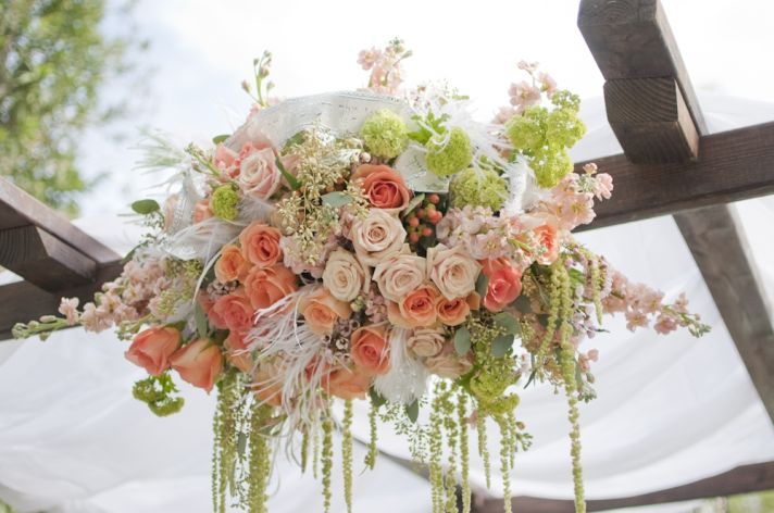 Romantic outdoor wedding ceremony arbor with peach ivory and blush pink