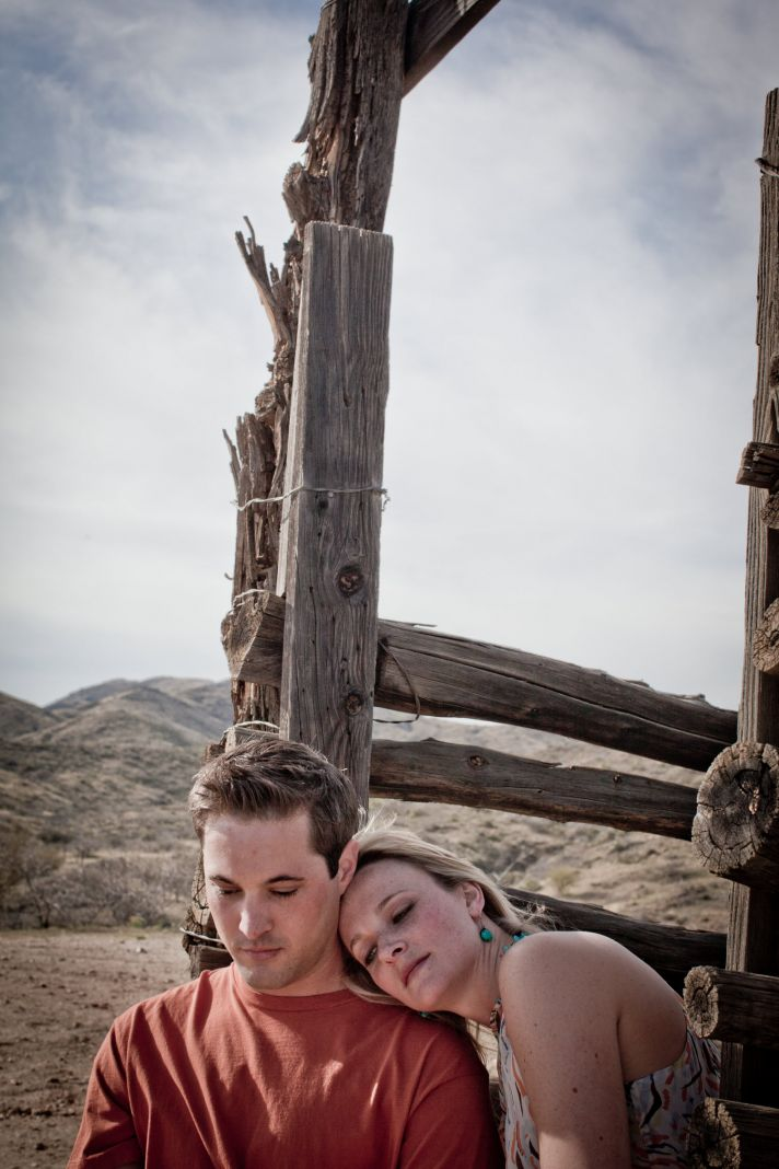 Beautiful bride and groom sit on vintage wagon during Arizona engagement session