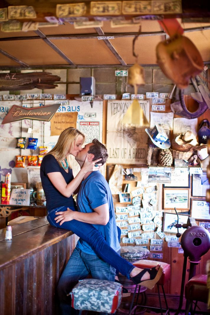 Arizona bride sits on bartop of old salloon, kisses groom-to-be