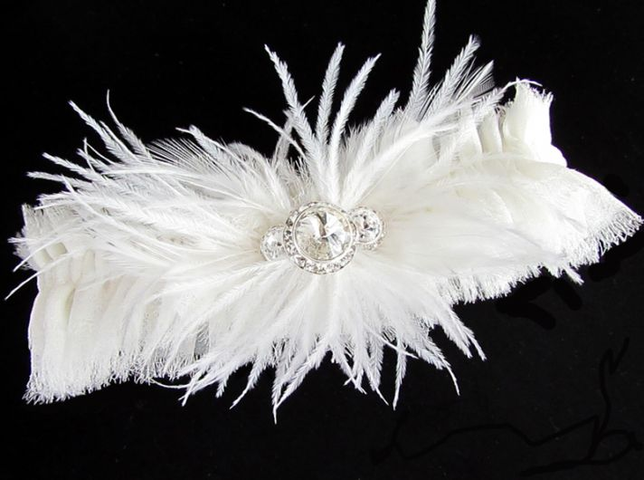 White wedding garter adorned with feathers and crystals
