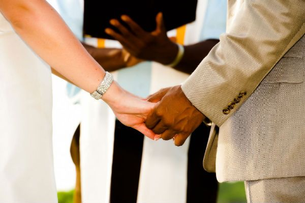 Bride and groom hold hands while taking wedding vows