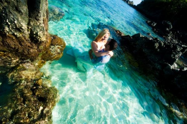 Bride in white wedding dress kisses groom in Caribbean ocean for trash the dress