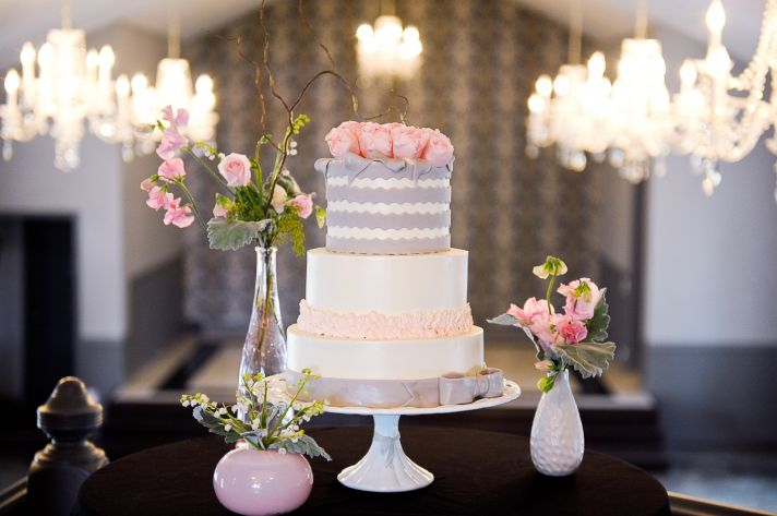 Classic white wedding cake, chandeliers hang from wedding venue