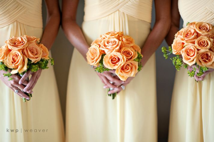 Bridesmaids wear pale yellow bridesmaids dresses, orange bridal bouquets