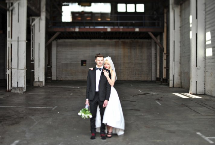 Quirky yet dapper grooms' wearing bow ties- bride and groom pose with urban backdrop